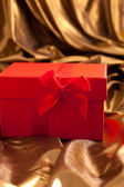 Red Valentines gift nestling in gold fabric — Stock Photo
