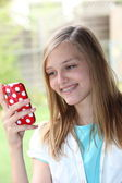 Teenage girl reading a text message on her phone — Stock Photo