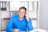 Young businessman talking on phone, at his desk — Stock Photo