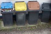 Four garbage bins colour coded for recycling — Stock Photo