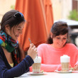 Stock Photo: Two attractive women enjoying cappuccino