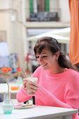 Pretty young woman enjoying a glass of cappuccino — Stock Photo
