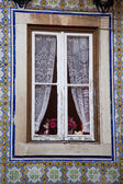 Window with lace curtains and ornate tiles — Stock Photo