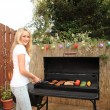 Stock Photo: Young womcooking on barbecue outdoors