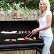 Stock Photo: Beautiful blond wombarbecuing on patio