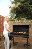 Young woman cooking on a barbecue outdoors — Stock Photo