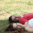 Stock Photo: Smiling happy teenage couple relaxing on grass