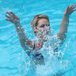 Young woman splashing in a swimming pool — Stock Photo