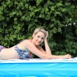 Stock Photo: Beautfiul womsunbathing poolside