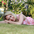 Stock Photo: Beautiful womlying on grass