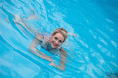 Beautiful young woman swimming in a pool — Stock Photo