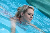 Beautiful woman floating in a swimming pool — Stock Photo