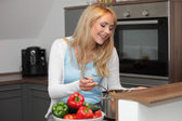 Housewife cutting fresh bell peppers into a cooking po — Stock Photo