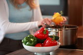 Housewife cutting fresh bell peppers — Stock Photo