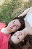 Two teenagers lying head to head on grass — Stock Photo