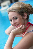 Beautiful young blond woman swimming in a pool — Stock Photo