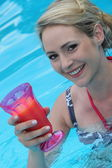 Beautiful young woman in a pool with a cocktail — Stock Photo