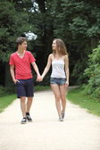 Attractive young teenage couple walking on a date — Stock Photo