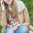 Attractive trendy shapely young teenage girl standing chatting on her mobile phone — Stock Photo #44184737