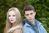 Young teenage couple posing back to back — Stock Photo