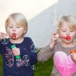 Two beautiful blond twins blowing bubbles — Stock Photo