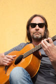 Man in sunglasses strumming a guitar — Stock Photo