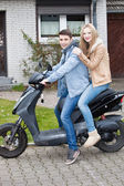 Attractive young teenage couple on a motorcycle — Stock Photo