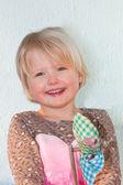 Laughing beautiful girl holding a toy pinwheel — Stock Photo