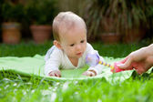 Cute little baby on a rug on green grass — Stock Photo