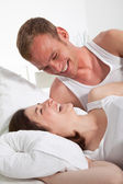 Happy Couple in Bed Next to One Another — Stock Photo