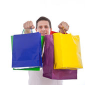 Excited man holding shopping or gift bags — Stock Photo