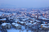 Town covered by snow at evening. Alba, Italy. — Stock Photo