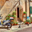 Постер, плакат: Motorcycle on cobbled street in Ventimiglia Italy