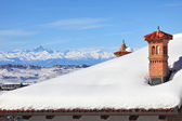 Red chimney on snowy roof. Piedmont, Italy. — Stock Photo