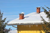 Red chimneys on snowy roof. Piedmont, Italy. — Stock Photo