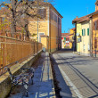 Bench on sidewalk and road through town in Italy. — Stockfoto