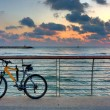 Royalty-Free Stock Photo: Bike on promenade against background of sunset sky and sea.
