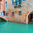 Narrow canal along old brick houses. Venice, Italy. — Stock Photo