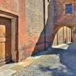 Cobbled street and red brick wall in italian town. — Foto Stock