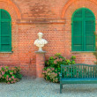 Wooden bench in front of red brick house in Italy. — Foto Stock