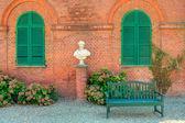 Banc en bois en face de la maison de briques rouges en italie. — Photo