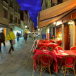 Stock Photo: Outdoor restaurant on narrow street in Venice, Italy.