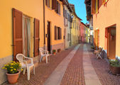 Narrow cobbled street among colorful houses in Italy. — Stock Photo