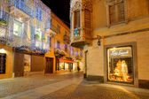 Illuminated street at night. Alba, Italy. — Stock Photo