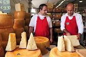 Cheesemakers 和在意大利干酪的轮子. — 图库照片