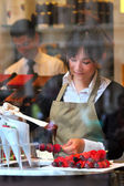 Confectionary worker pouring hot chocolate on strawberries. — Stock Photo