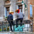 Stock Photo: Two gondoliers on bridge in Venice.