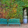 Benches and sculpture in autumnal park, — Stock Photo