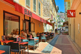 Narrow street with restaurants in Menton. — Stock Photo