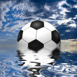 Soccer ball reflected in water over the blue sky with clouds — Stock Photo #12980394